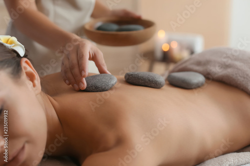 Leinwanddruck Bild Beautiful young woman getting hot stone massage in spa salon