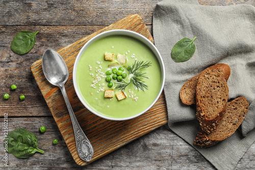 Leinwandbild Motiv Fresh vegetable detox soup made of green peas served on table, top view