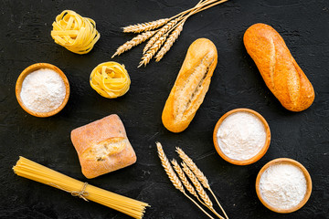 Homemade fresh bread and pasta near flour in bowl and wheat ears on black background top view