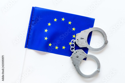 Leinwanddruck Bild Violation of law, law-breaking concept. Metal handcuffs on European flag on white background top view