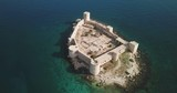 High angle aerial view point of interest clockwise rotating above the turquoise sea water surrounding Kizkalesi Castle island on sunny day in Turkey. 4K at 23.97fps - 235051502