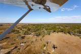 rundflug über okavangodelta in botswana afrika mit schatten vom flugzeug und einem teil der tragfläche vor blauen himmel