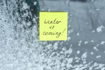 Winter is coming, texture background snow-covered window with a sticker.