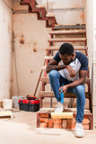 african american man sitting on stairs with roller brush during renovation of home