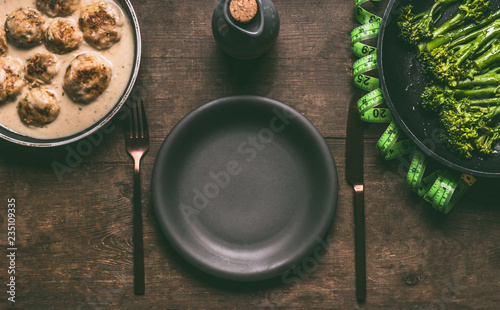 Empty plate with cutlery and low carb dieting meal with meat balls, blanched broccoli in cooking pan and measure tape on wooden table background, top view with copy space. Healthy weight loss diet - 235109335