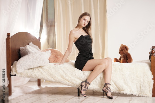 Leinwanddruck Bild beautiful slim young woman posing on her white bed in the bedroom at home