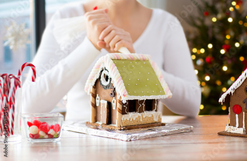 Leinwandbild Motiv cooking, holidays and people concept - woman with pastry bag making gingerbread houses at home over christmas tree lights background