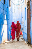 Two women dressed in the traditional Indian Sari are walking through the narrow streets of the blue city of Jodhpur, Rajasthan, India.