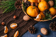 Hazelnuts, walnuts and tangerines decorated with Christmas branches and pine cones on the table in a wooden basket