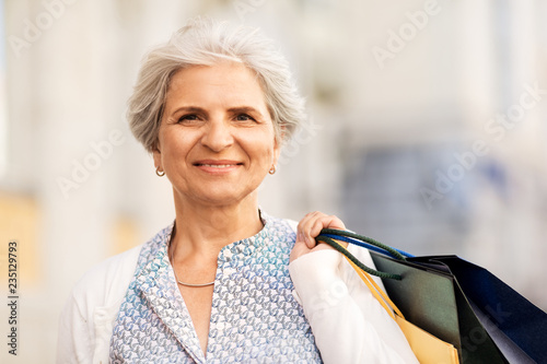 fototapeta na ścianę sale, consumerism and people concept - senior woman with shopping bags in city