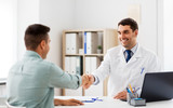 medicine, healthcare and people concept - smiling doctor and male patient shaking hands at hospital