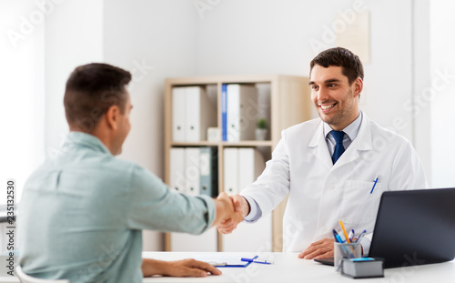 medicine, healthcare and people concept - smiling doctor and male patient shaking hands at hospital © Syda Productions