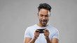 technology, gaming and people concept - happy indian man playing game on smartphone over grey background