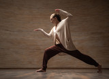 Calm young woman in comfortable clothes standing in the room alone and practicing chi gong - 235142915