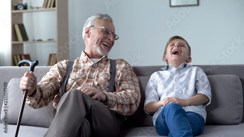 Leinwanddruck Bild Old man and boy laughing genuinely, joking, valuable fun moments together