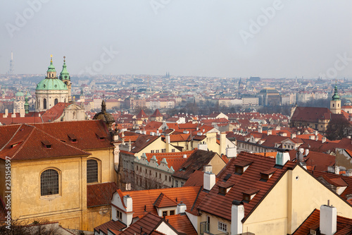 Peaceful view of Mala Strana in Prague with red tiled roofs and the baroque church of Saint Nicholas