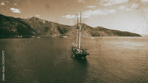 Old sailing ship anchored near an island, aerial view in black and white