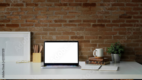 Creative desk workspace with blank picture frame poster, blank screen laptop for graphic display montage - 235157319