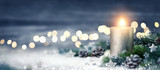 Dekoration für Weihnachten mit Kerze und Lichtern auf Schnee und Holz