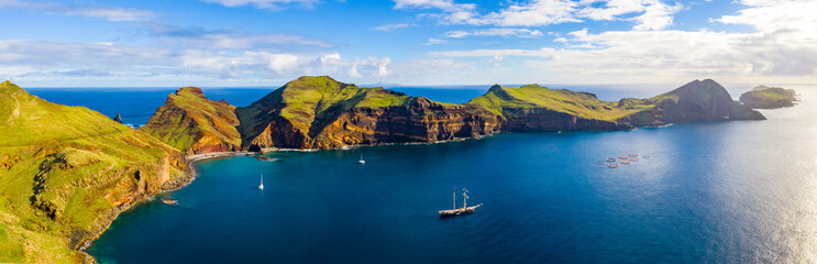 Aerial tropical island view in the middle of the ocean with rocky cliffs and green fields © ingusk