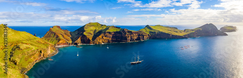 Aerial tropical island view in the middle of the ocean with rocky cliffs and green fields - 235183344