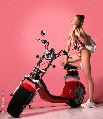 Sexy girl with perfect body on red motobike