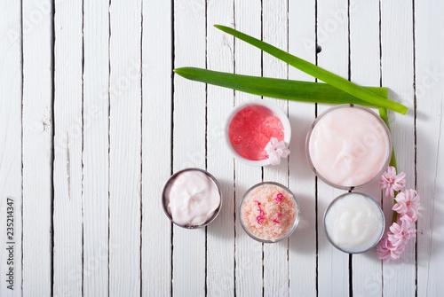 kremy kosmetyczne i kosmetyczne z różowymi kwiatami na białym drewnie