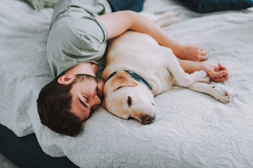 Pleasant young man enjoying his sleep while embracing his dog