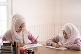 islam education concept, Adult muslim female teaching with art to learning a child girl in home.