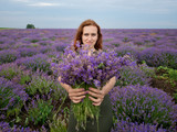 Young girl with a bouquet in hands, posing in a lavender field.