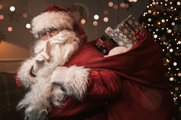 Santa Claus with finger on the lips gesturing shh sign
