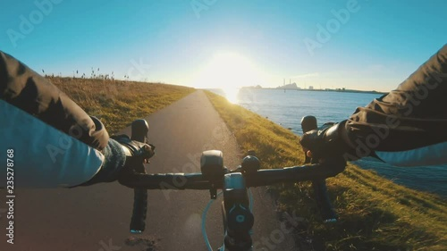 Riding racing bicycle close to the sea while the sun sets
