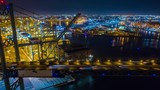 Aerial time lapse of a shipyard or harbor with container ships unloading cargo and night - 235285171
