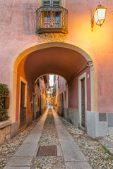 Beautiful scenic alley with historic and traditional houses and cobbled street. Picturesque Italian village, Orta San Giulio (street Giovanetti), on lake Orta, north Italy © AleMasche72