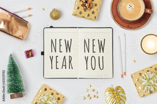 New Year resolutions concept with notepad and gift boxes on white background