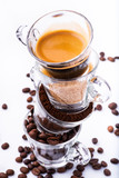 glass cups, in vertical sequence, with coffee beans, ground coffee, brown sugar and a creamy drink. still life