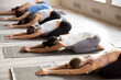Leinwandbild Motiv Group of young sporty people practicing yoga, doing Child exercise, Balasana pose, working out, indoor full length, mixed race female students training at club or studio. Well being, wellness concept