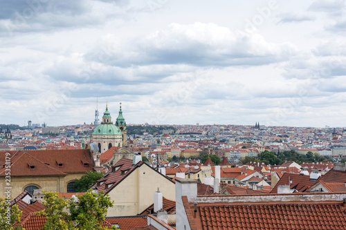 Prague panorama with colorful rooftops on a cloudy day, with The Church of St. Nicholas and Zizkov television tower in the distance