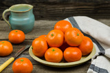 Clementines. Still life with tangerines on a plate, rustic background