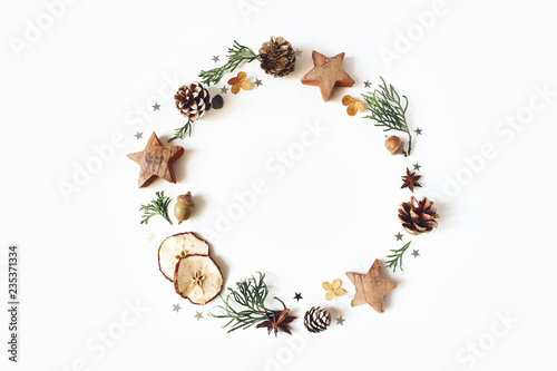 Leinwandbild Motiv Christmas circle floral composition. Wreath of cypress branches, pine cones, anise, confetti stars, dry apples and hydrangea flowers on white background. Winter wedding design. Flat lay, top view.