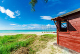 gorgeous beautiful inviting Cuban Varadero beach and tranquil turquoise ocean with brownish red wooden shed on blue sky background, sunny day