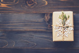 String or twine tied in a bow on kraft paper. Above gift box on wood with space. - 235388728