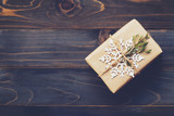 String or twine tied in a bow on kraft paper. Above gift box on wood with space. - 235388739