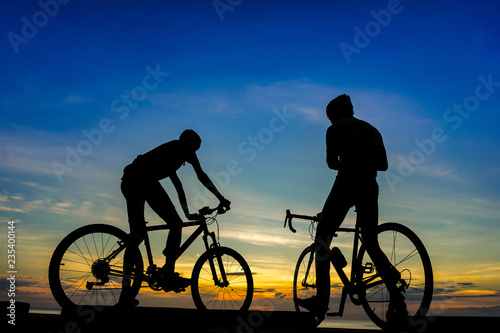 Cyclists with bicycles at the beach, at dusk.