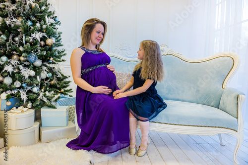 adbd2550258d9 Beautiful pregnant woman in ultra violet dress sitting with doughter ...