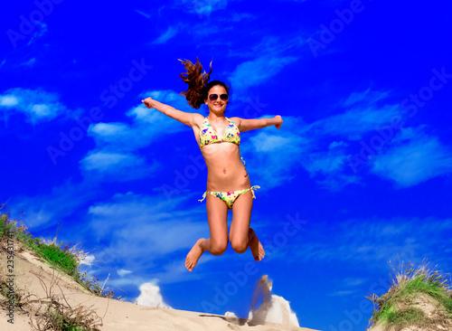 Leinwandbild Motiv Attractive Girl in Bikini Jumping on the Beach Having Fun, Summer vacation holiday Lifestyle. Happy women jumping freedom on sand.
