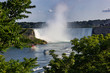Wide view of the beautiful American side of the Niagara falls and a boat in front of it, from the Canadian side.