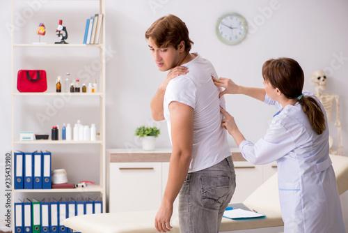 Leinwandbild Motiv Male patient visiting young female doctor chiropractor