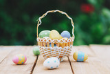 Colorful easter eggs in basket on wooden table win copy space. - 235446504