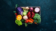 Leinwanddruck Bild - Fresh vegetables and fruits in a wooden box on a black background. Organic food. Top view. Free copy space.
